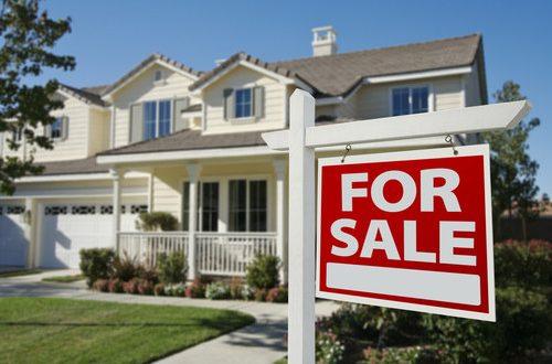 casa-con-un-letrero-de-venta-en-frente