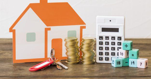 casa-llave-monedas-apiladas-calculadora-bloques-matematicas-mesa-madera_23-2147863938