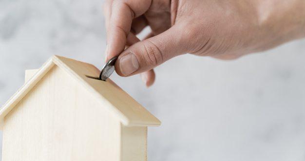 primer-plano-mano-persona-insertando-moneda-alcancia-casa-madera_23-2148038721