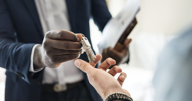 Real estate agent handing the house key to a client