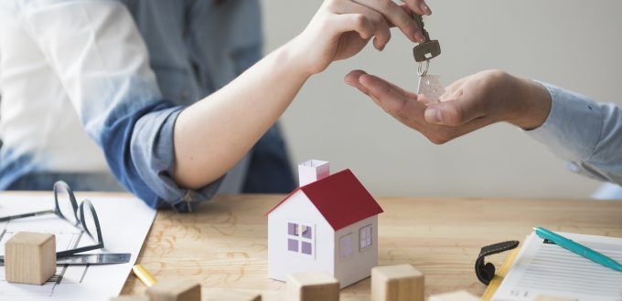 close-up-of-woman-s-hand-giving-house-key-to-man-over-wooden-table