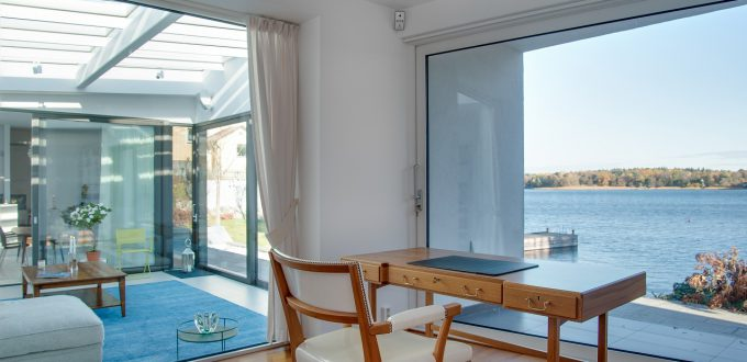 A luxury beach house with glass windows and the beautiful scenery of the sea in the background