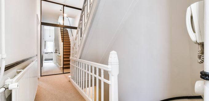Residential house second floor with staircase and white fence against mirrored sliders of closet